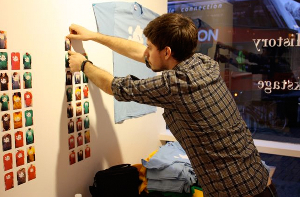 Gallery assistant putting up a photo